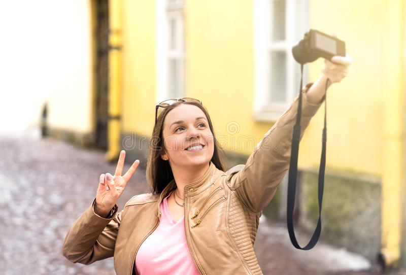 Vlogger filming video blog in city. Young smiling happy woman. stock photography