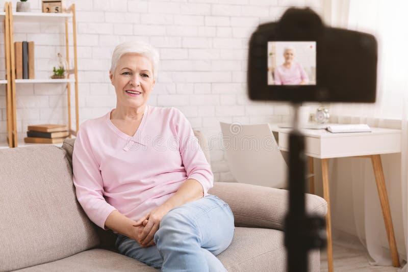 Vlogger mayor amistoso de la mujer que se sienta en la dataci?n del sof? en l?nea foto de archivo libre de regalías