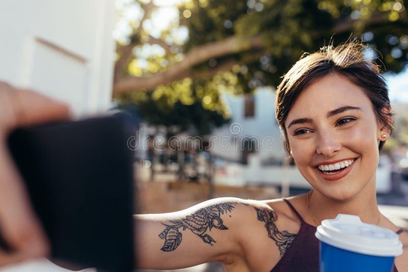 Vlogger som tar selfie med hennes smarta telefon royaltyfri bild