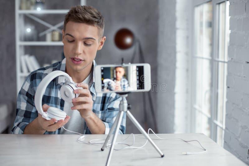 Vlogget concentrado que muestra sus auriculares en la leva fotos de archivo libres de regalías