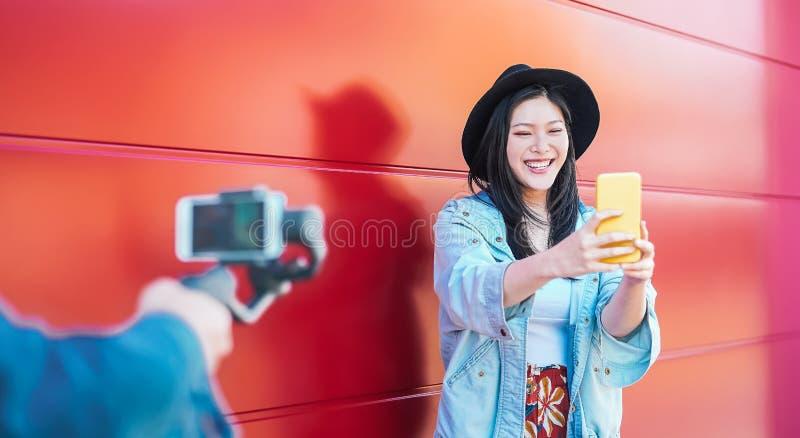 vlogging和使用流动智能手机的亚裔时尚妇女室外-获得愉快的中国时髦的女孩做录影的乐趣 免版税库存照片