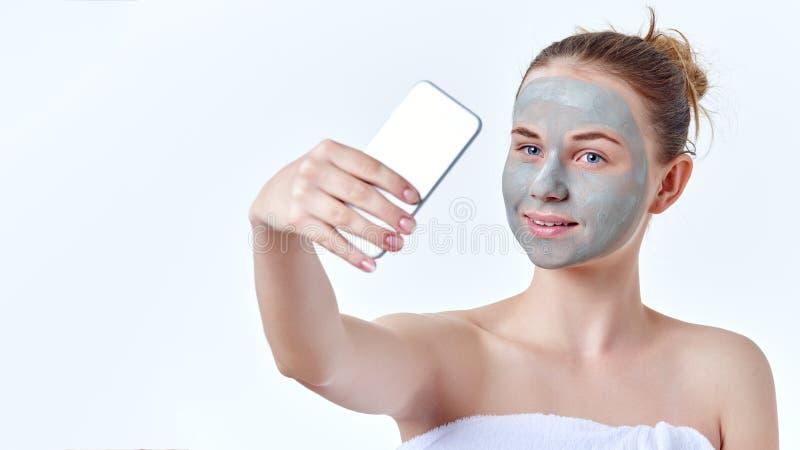 Vlogging pojęcie Młoda rudzielec nastoletnia dziewczyna z wysuszoną twarzy maską na jej twarzy używać jej mądrze telefon robić wi obraz royalty free