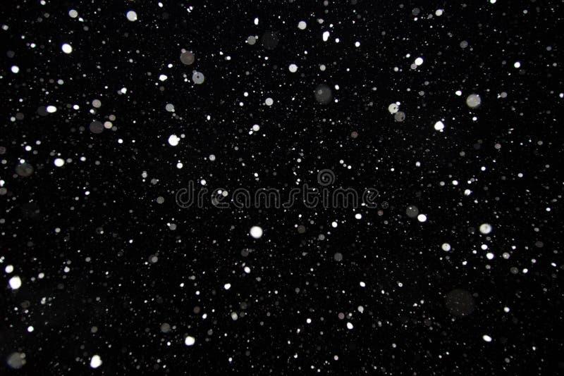 Vlokken van sneeuw op een zwarte achtergrond Sneeuwval, sneeuwvlokkentextuur stock afbeelding