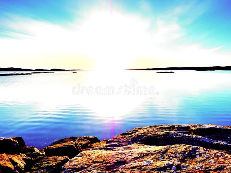 Vlotte avondoverzees tussen granietrotsen Vreedzame Achtergrond met Rustig Kalm Water stock afbeelding