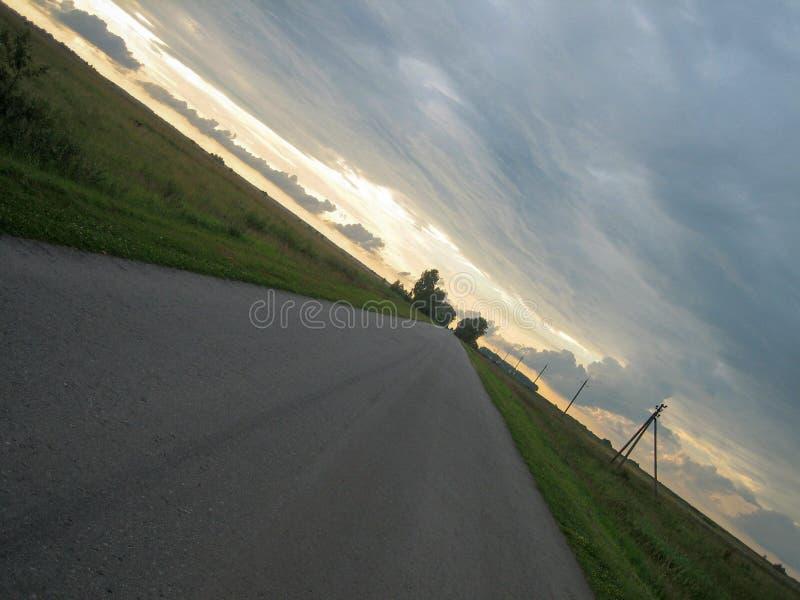 Vlotte rechte asfaltweg in het platteland onder de hemel met wolken bij zonsondergang royalty-vrije stock foto