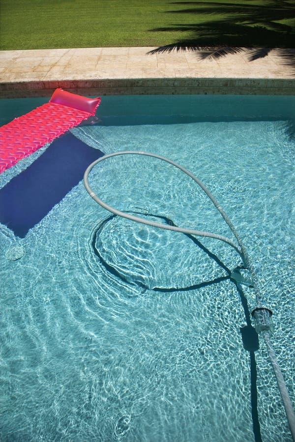 Vlotter en vacuümslang in pool. stock fotografie