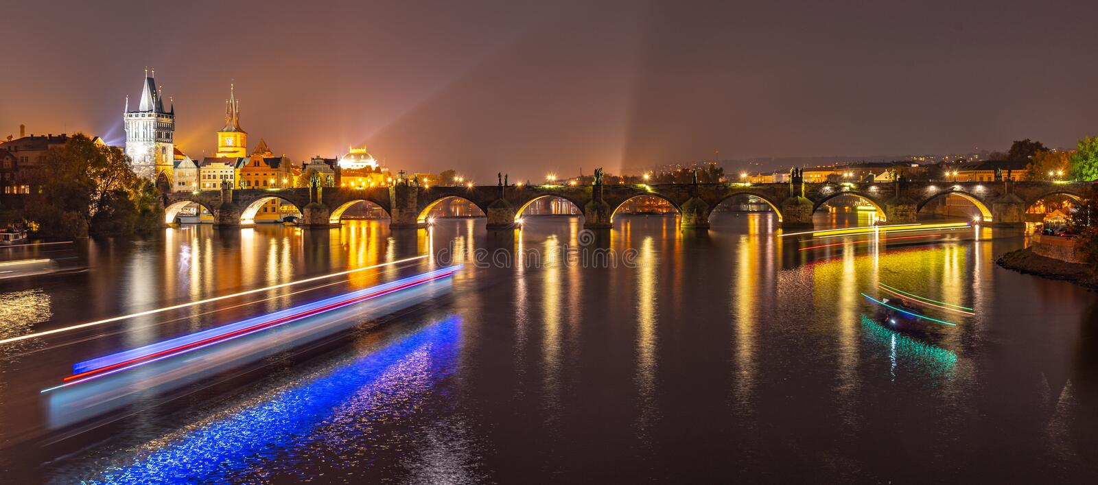 Vltava River with boat neon light lines and Charles Bridge with Old Town Bridge Tower by night, Prague, Czechia. UNESCO stock images
