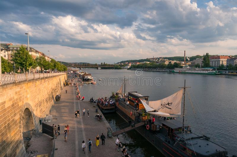 Vltava river waterfront promenade with restaurant and people walking royalty free stock photo