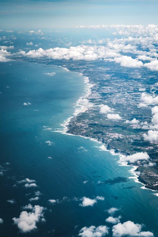Vlucht over de kust van het gebied van Portugal Lissabon Satellietbeeld door het vliegtuigvenster met wolkenwater en royalty-vrije stock foto