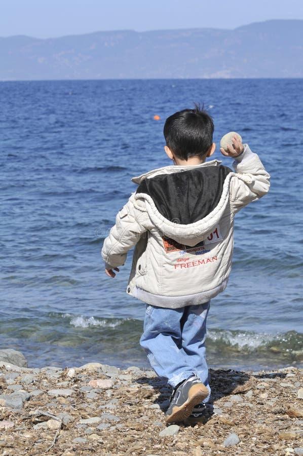 Vluchtelingsjongen die rots op zee Lesbos Griekenland werpen royalty-vrije stock afbeelding