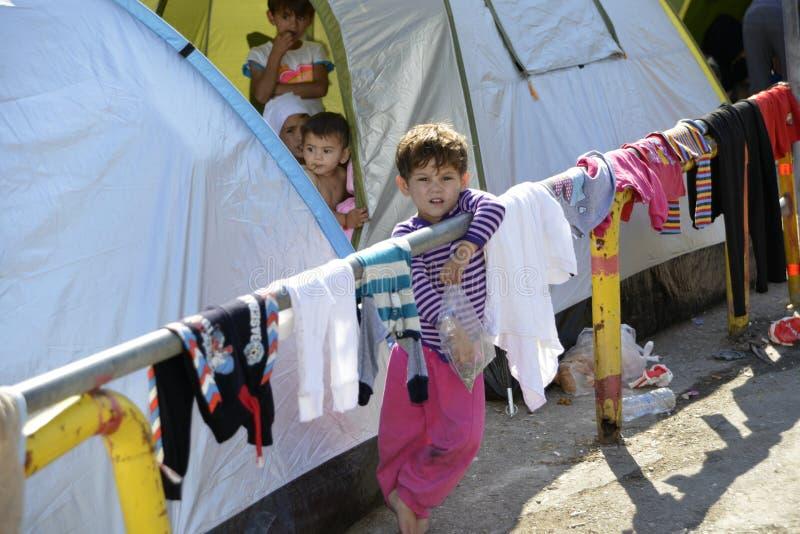 Vluchtelingskind voor tent Lesvos Griekenland stock foto