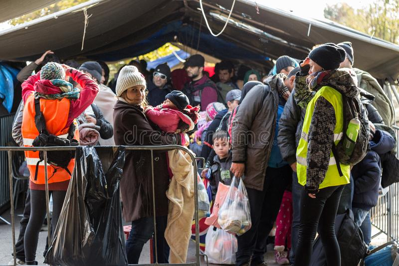 Vluchtelingsvrouw die haar kind, een baby houden, die zich in het midden van een menigte op de grens van Kroatië Servië, op de Ro stock fotografie