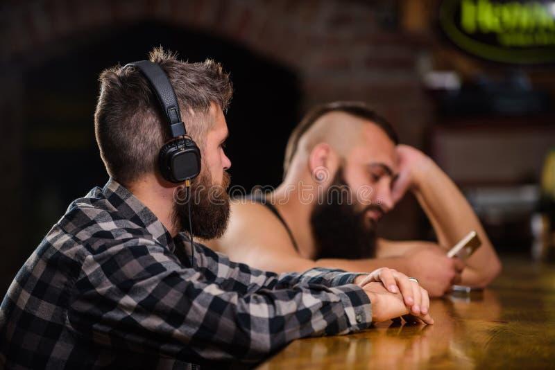 Vluchtwerkelijkheid Vrijdagontspanning in bar Besteedt de Hipster gebaarde mens vrije tijd bij barteller Ordedranken bij bartelle stock foto's