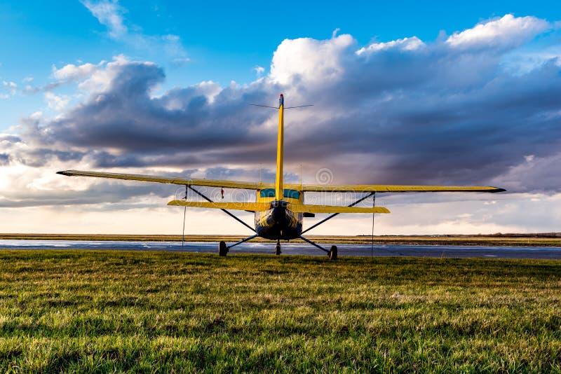 Vlugge Stroom, SK/Canada- 10 Mei, 2019: Geel Cessna-Vliegtuig in stormachtige hemel stock afbeelding