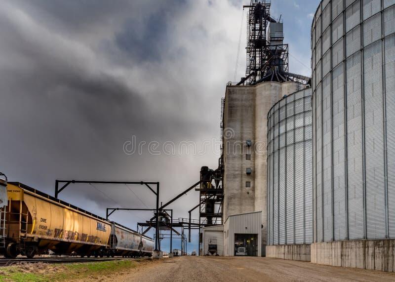 Vlugge Stroom, SK/Canada- 10 Mei, 2019: Het semi leegmaken met stormachtige hemel in Paterson Grain Terminal in Vlugge Stroom, SK royalty-vrije stock foto