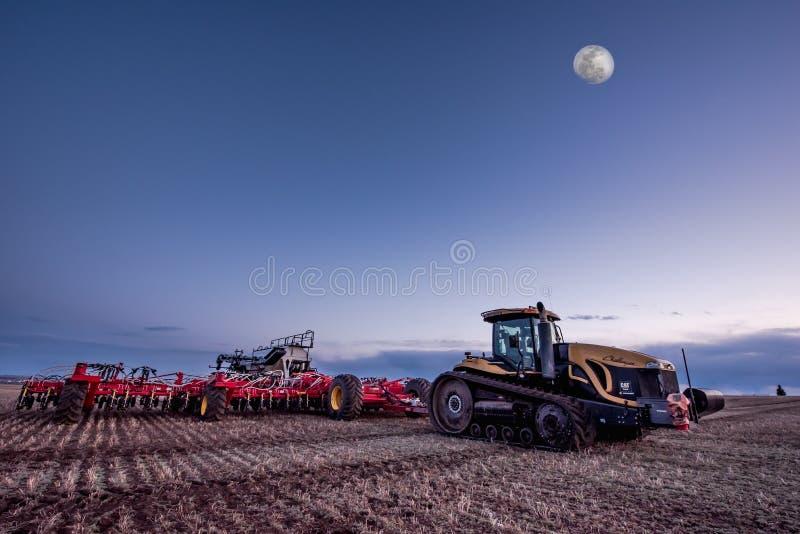 Vlugge Stroom, SK/Canada- 10 Mei, 2019: Volle maan over Caterpillar-tractor en de luchtdrukboor van Bourgault op het gebied royalty-vrije stock foto