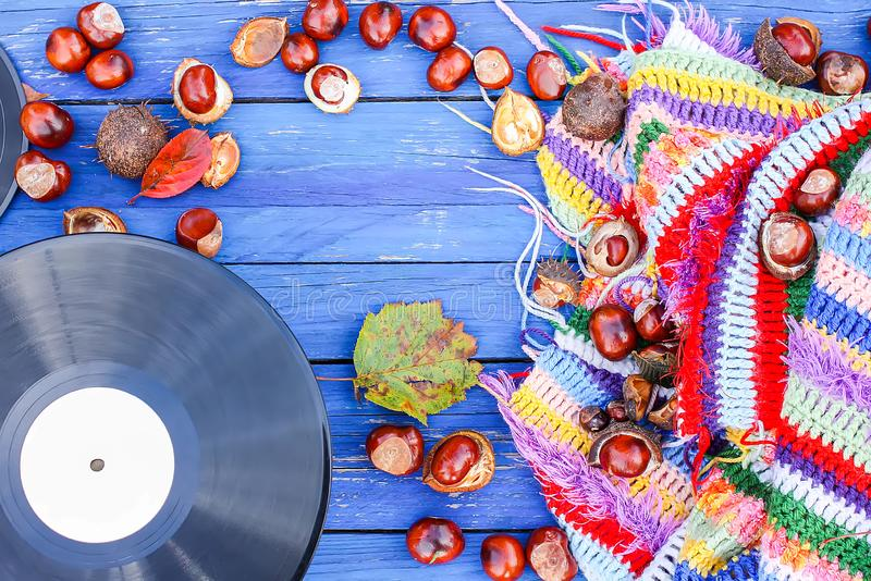 Vntage vinyl records on aged wooden background with bright handmade crocheted plaid, chestnuts and fall leaves. Vntage vinyl records on aged wooden background royalty free stock images