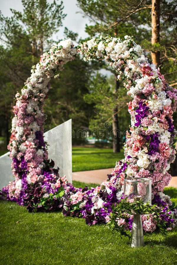 Voûte de mariage des fleurs avec des torches à une cérémonie extérieure photo libre de droits