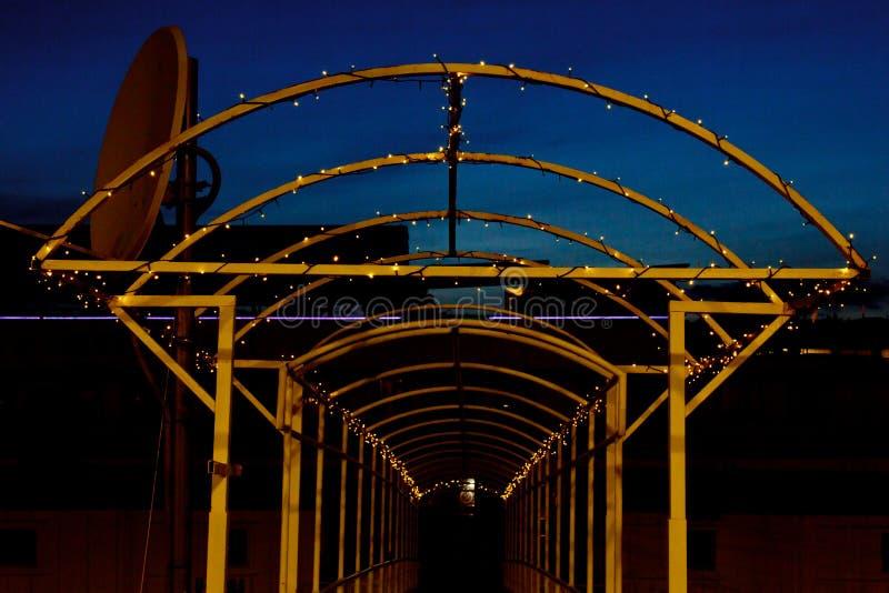 Voûte en métal enlacée avec une guirlande avec des lumières de LED la nuit manière dans la perspective photos stock