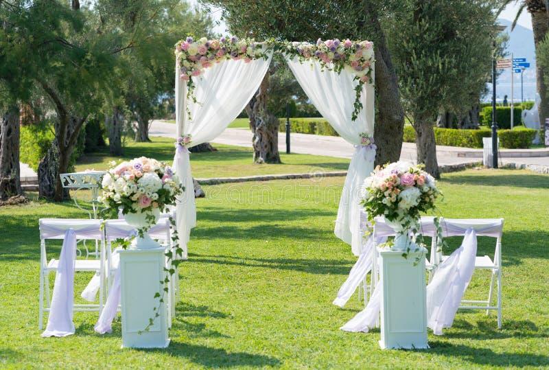 Voûte l'épousant en bois rectangulaire décorée des fleurs et du tissu pour une cérémonie l'épousant sur le pré photo libre de droits