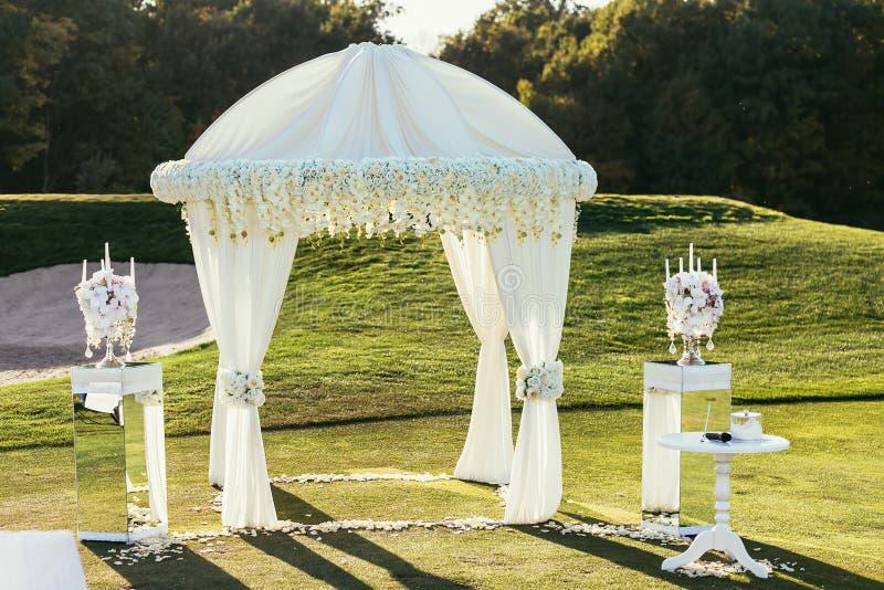 Voûte blanche de mariage avec des fleurs et décoration de bougie sur ensoleillé images libres de droits