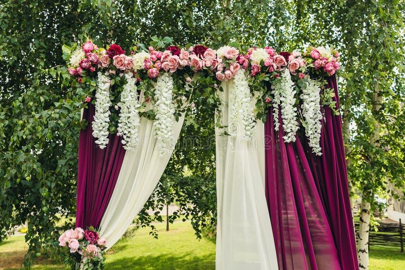 Voûte de mariage avec des fleurs situées dans la cérémonie de mariage de forêt i images stock