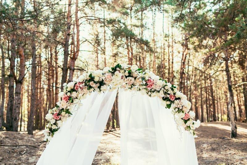 Voûte de mariage avec des fleurs situées dans la forêt sur la cérémonie de mariage photographie stock libre de droits