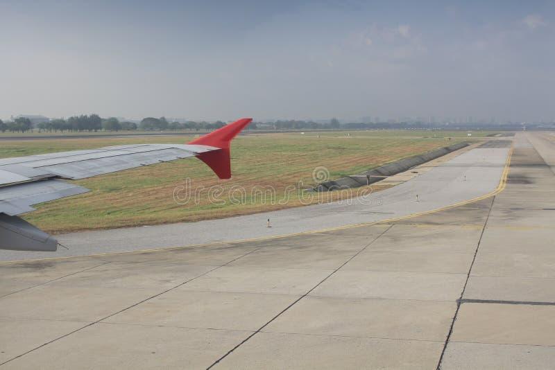 Voando e viajando no exterior, vista aérea da janela do avião na asa do jato na pista de decolagem do aeroporto fotografia de stock