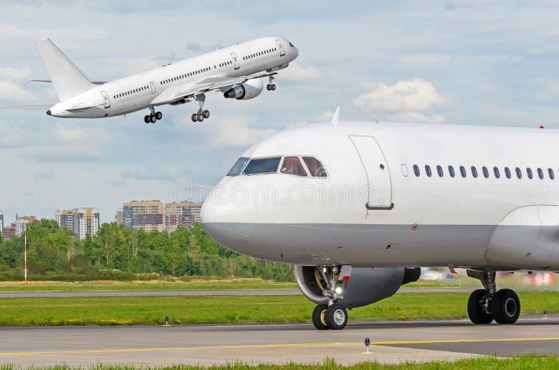 Voar decola o plano e um outro táxi taxiing da cabina do piloto do close-up do avião ao terminal fotos de stock