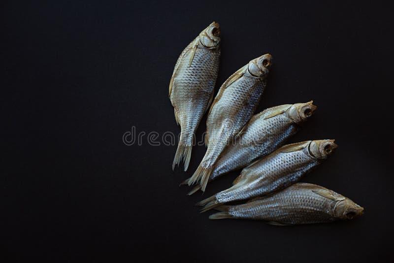 Vobla secco del pesce salato su un fondo nero Triotto caspico immagini stock