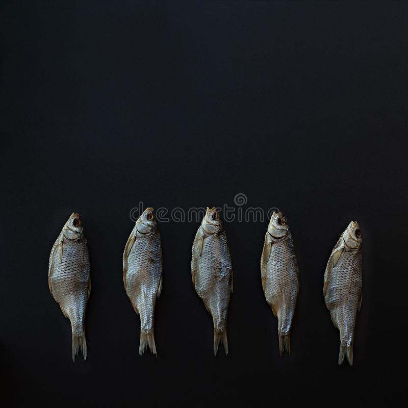 Vobla secco del pesce salato su un fondo quadrato nero Triotto caspico immagini stock