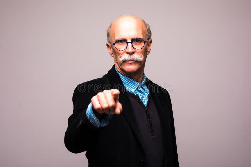 Você é o seguinte Homem maduro seguro no formalwear que aponta o ao estar contra o fundo cinzento imagens de stock royalty free
