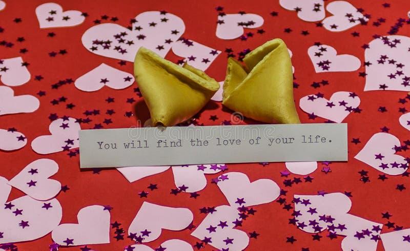 ` Você encontrará o amor de sua mensagem do ` da vida em cookie de fortuna quebrada no fundo vermelho coberto com os cervos imagem de stock royalty free