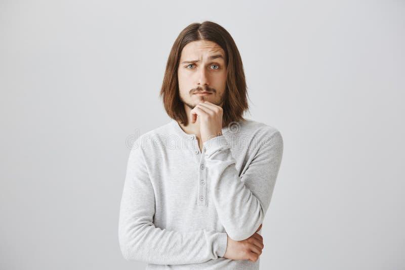 Você fez-me interessou e curioso, diga detalhes Retrato do homem novo considerável com a barba e o cabelo longo que guardam a mão imagens de stock