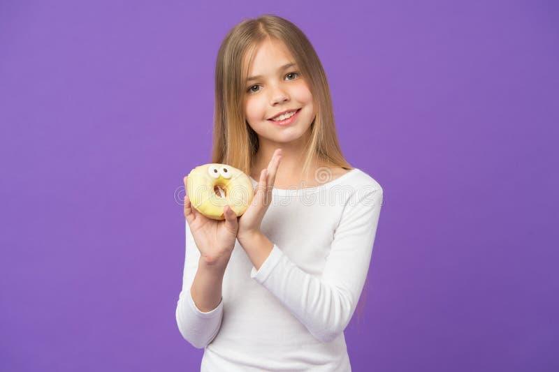 Você quer uma mordida? Criança feliz com comida lixo Sorriso da criança com a filhós no fundo violeta Menina com a filhós vitrifi imagem de stock