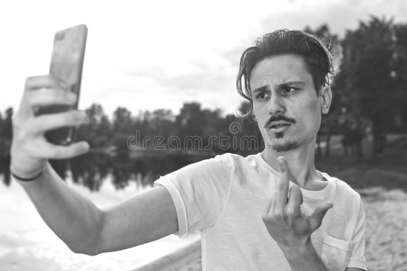 Você terá o homem dos problemas O retrato de agressivo confuso irritado no indivíduo mau do humor fala irritably no telefone no f fotos de stock royalty free