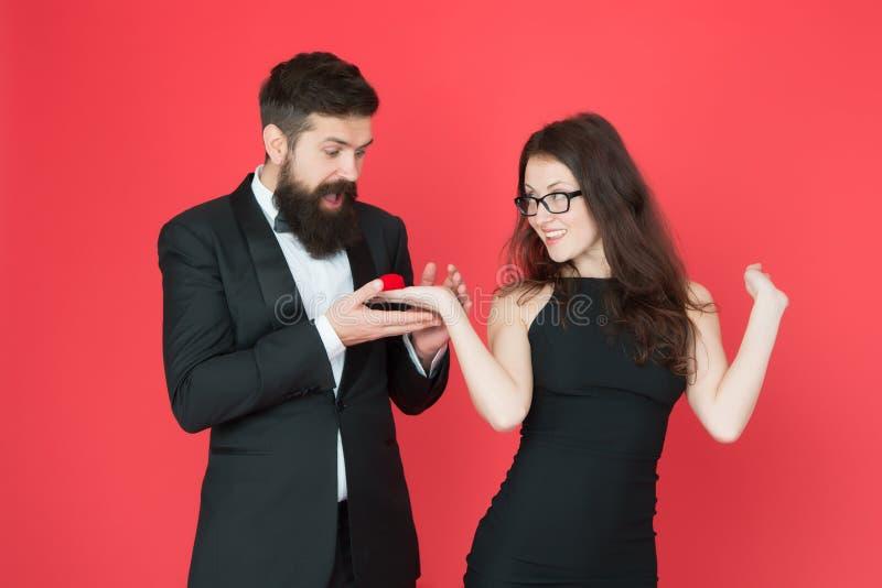Voc? casar-me-? mulher para fazer a proposta farpada do homem Pares formais Anel na caixa Rosa vermelha Pares 'sexy' fotografia de stock royalty free