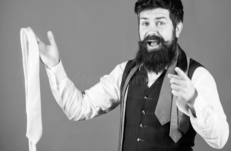 Voc? deve compr?-lo Assistente de loja que aponta o dedo e que oferece a variedade larga das gravatas para comprar bearded imagens de stock royalty free