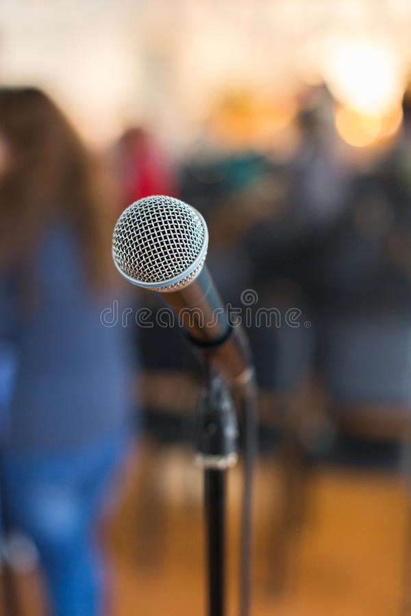 Vocal Microphone in focus against blurred audience at the conference. Or live concert stock image
