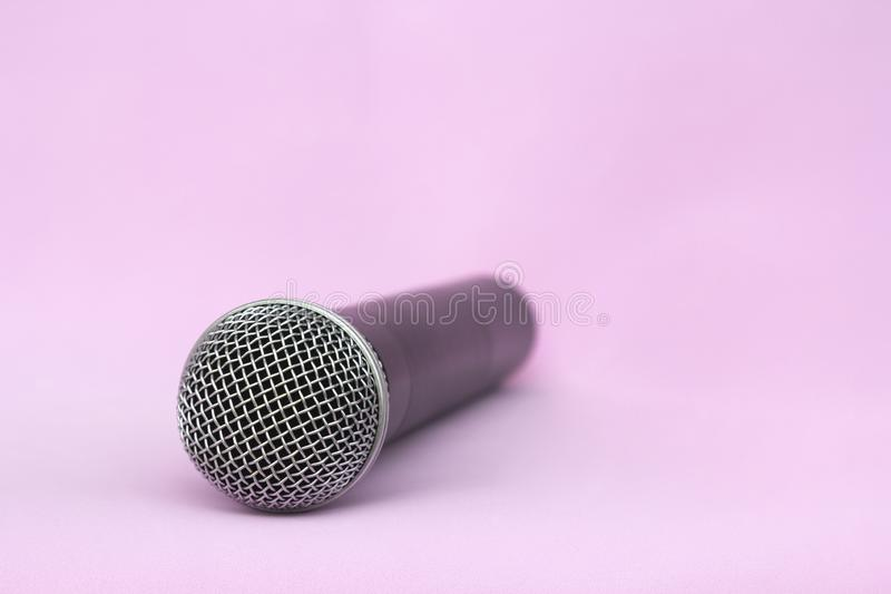 Vocal silver microphone wireless for audio recordings, karaoke on pink background stock photo