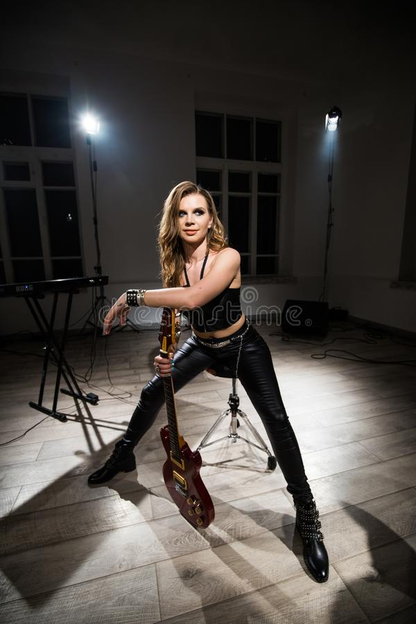 Vocalist in leather clothes sitting in the studio with light and musical instruments. royalty free stock photo