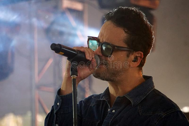 Vocalist of Los amigos invisibles. Julio Briceño, vocalist of the latin american rock group called los amigos invisibles, male singer holding a microphone in stock photos