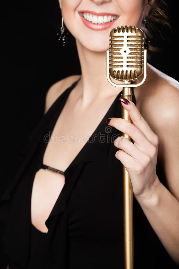 Vocalista hermoso de la muchacha con la sonrisa que celebra el microp de oro del vintage imagen de archivo libre de regalías