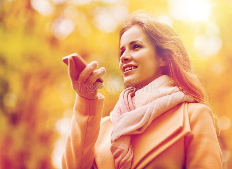 Voce della registrazione della donna sullo smartphone nel parco di autunno fotografia stock libera da diritti