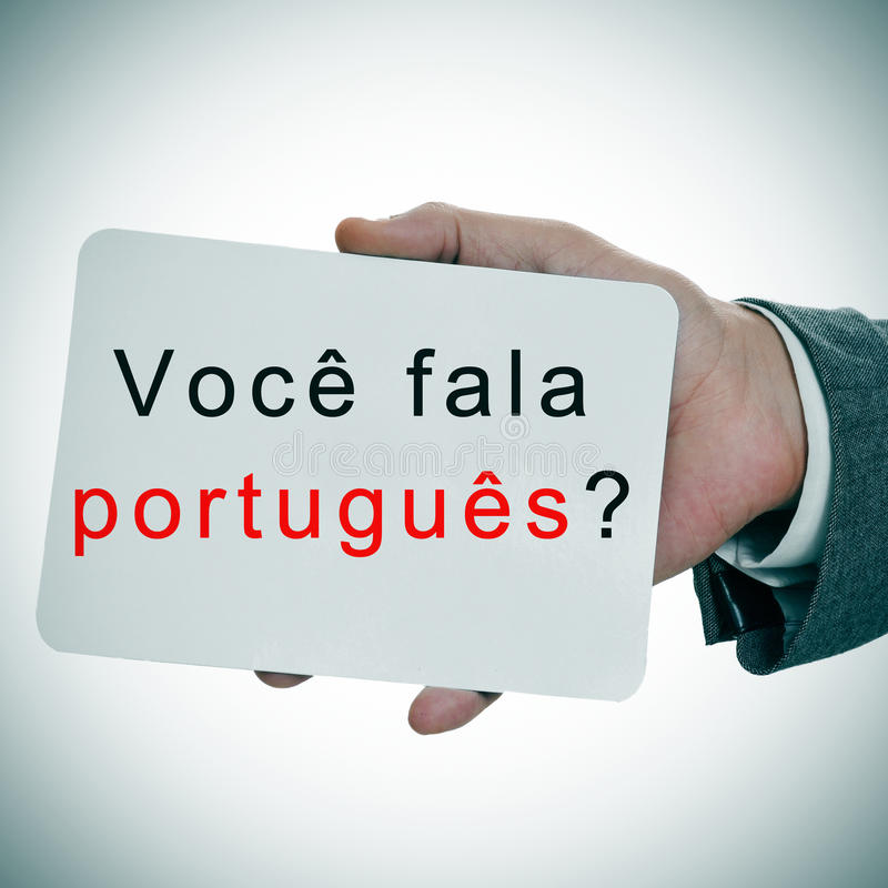 Voce fala portugues? do you speak portuguese written in portuguese. Man hands showing a signboard with the sentence voce fala portugues? do you speak portuguese royalty free stock photos