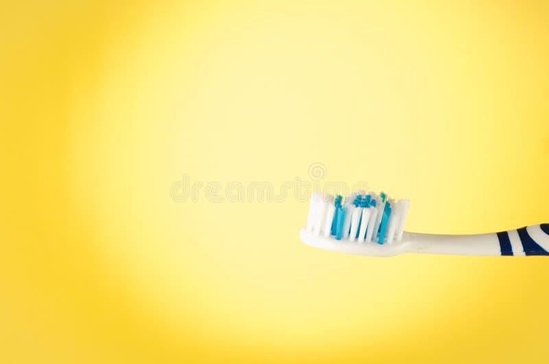 Vochtige tandenborstel op een gele achtergrond met exemplaarruimte royalty-vrije stock foto