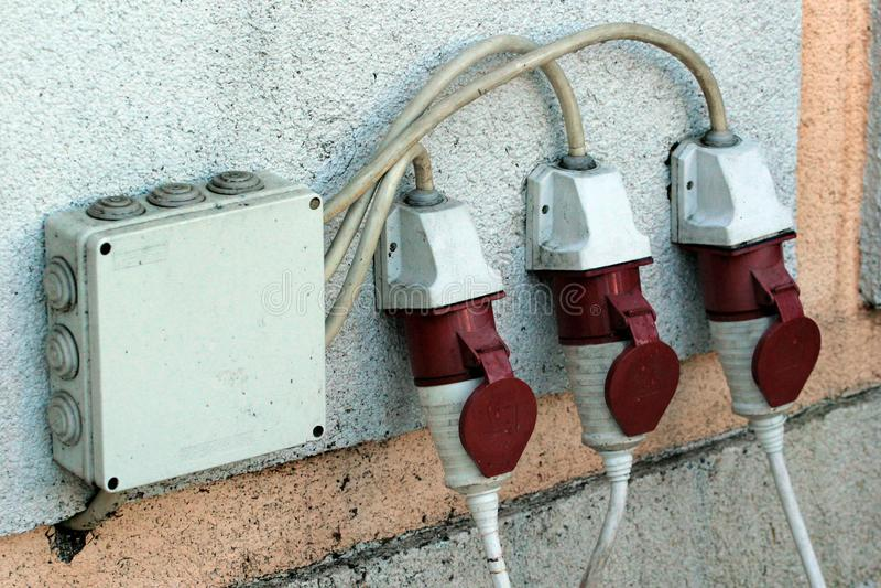 Vochtigheid drie beschermde elektroafzet op een buitenmuur stock afbeelding