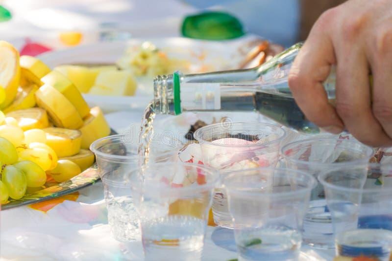 A vodca é derramada em vidros plásticos Uma garrafa em uma mão do ` s do homem foto de stock