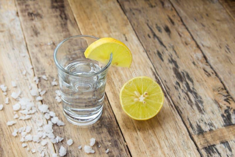 Vodca com o limão no fundo de madeira fotos de stock royalty free