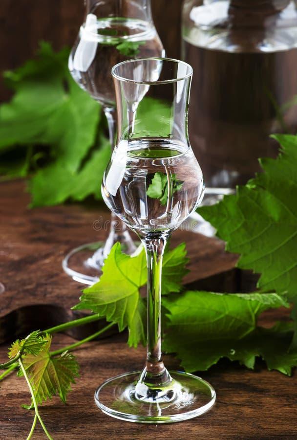 Vodca da uva, pisco - bebida alcoólica forte peruana tradicional em vidros elegantes na tabela de madeira do vintage, espaço da c imagem de stock